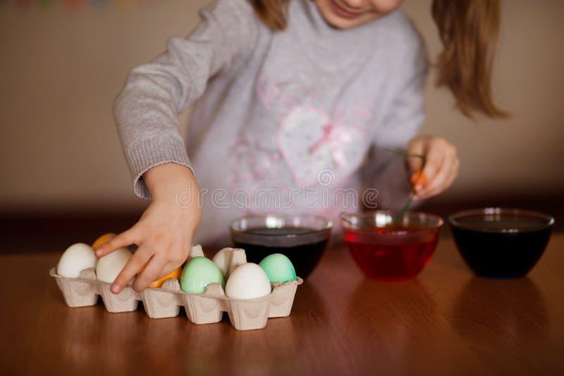 пасха счастливая Художник маленькой девочки покрасил яйца Ребенк подготавливая для пасхи покрашенная рука Краска пальца Концепция стоковые фото