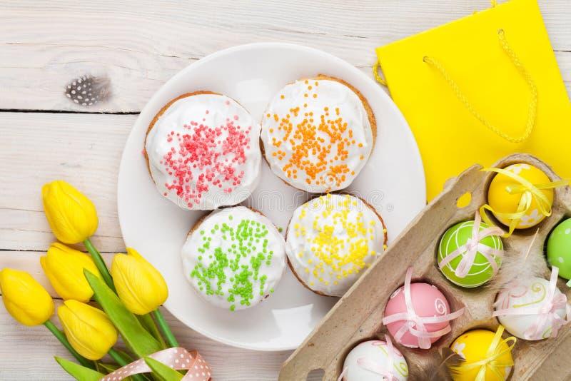 Пасха с желтыми тюльпанами, красочными яичками и традиционными тортами стоковая фотография rf