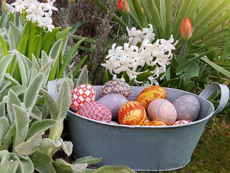 Пасха украсила яйца в винтажной корзине металла в цветочном саде стоковое фото rf