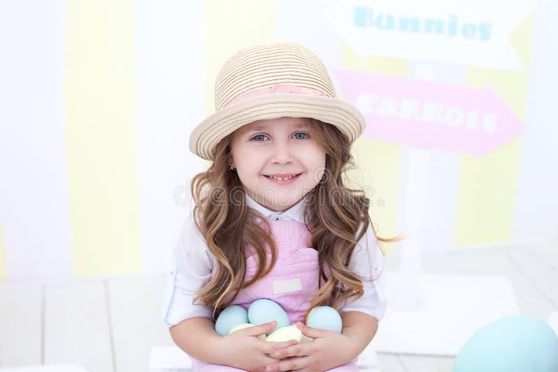 Пасха! Усмехаясь девушка держит много красочные яйца в ее руках на фоне интерьера пасхи Пестротканое Eas стоковая фотография rf