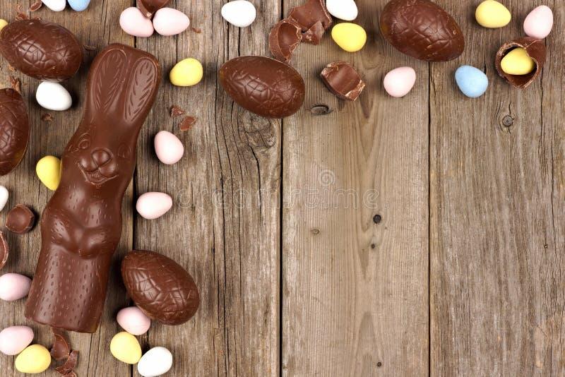 Пасхальное яйцо шоколада и граница зайчика угловая против деревенской древесины стоковые фотографии rf