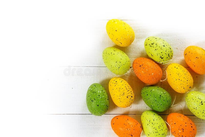 Пасхальные яйца в зеленом цвете, желтом цвете и апельсине на белой древесине, угловом ба стоковые фотографии rf
