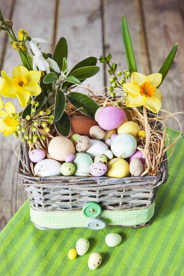 Пасхальные яйца в корзине на зеленой striped ткани стоковое изображение rf