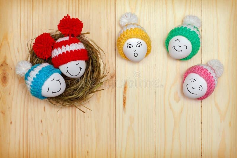 Пасхальные яйца в покрашенных крышках на деревянном столе, с эмоциями человеческого лица стоковые изображения rf
