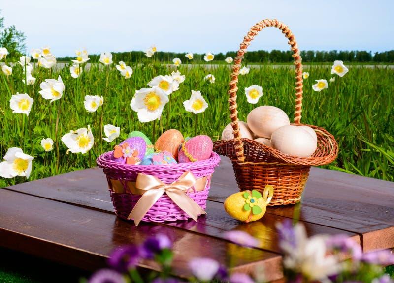 Пасхальные яйца и подготовки для яичек на деревянном столе и корзине стоковая фотография