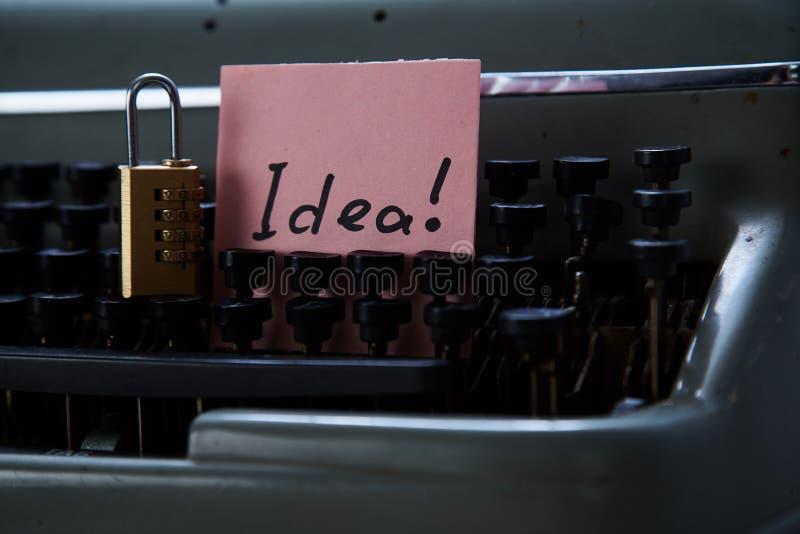 Патент, авторское право или интеллектуальная концепция защиты: идея надписи и замок лежа на машинке стоковые фото