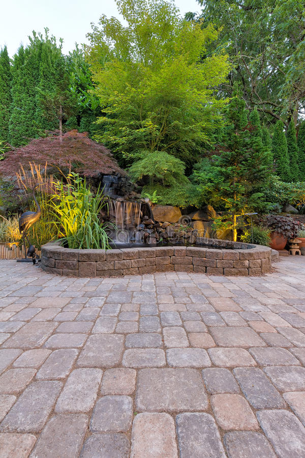 Патио кирпича Paver с прудом водопада стоковые фотографии rf
