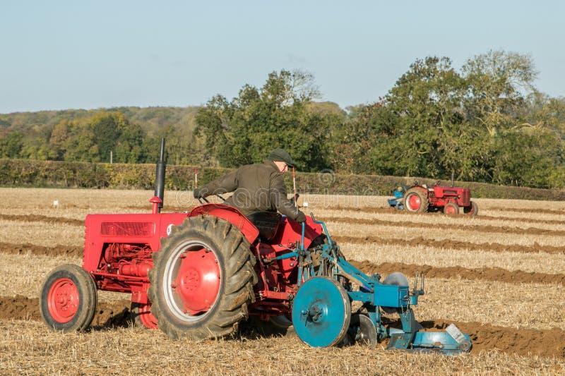 Пахать 2 старый винтажный красный тракторов стоковые изображения rf
