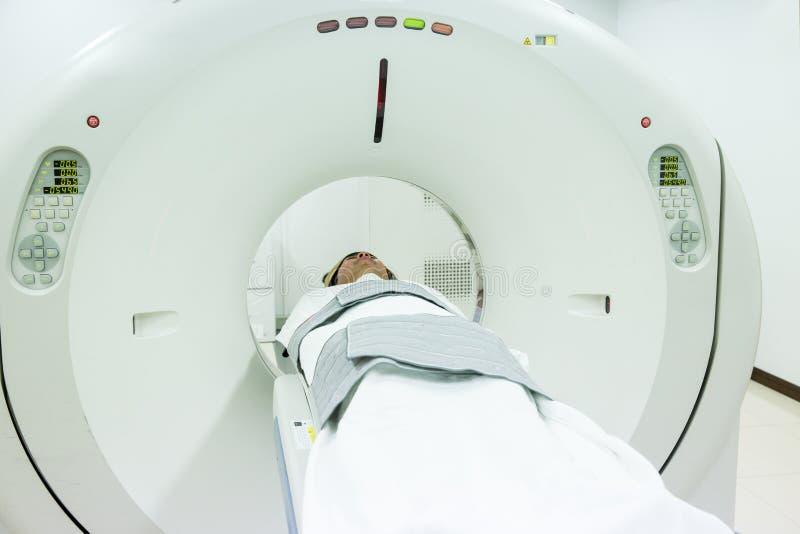 Пациенты экранируя на блоке развертки CT Человек проходя развертку CT пока ` s доктора используя компьютеры стоковые изображения