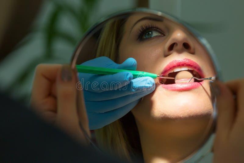Пациент восхищает ее улыбку смотря зеркало стоковое фото rf
