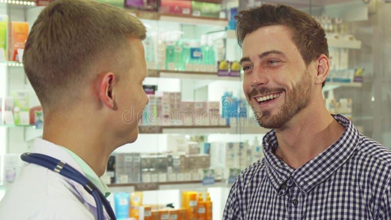 Пациент говоря к доктору и смеясь над на аптеке стоковое изображение rf