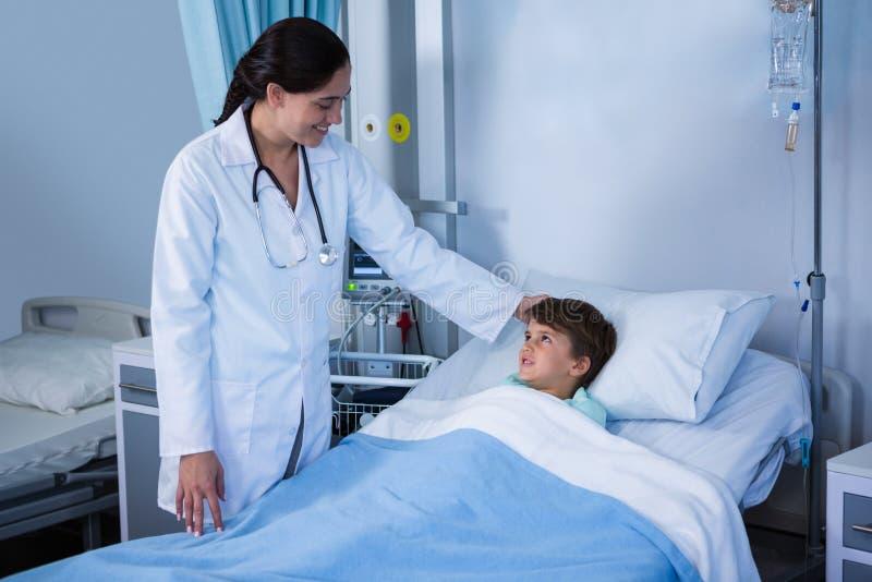 Пациент женского доктора утешая во время посещения в палате стоковая фотография