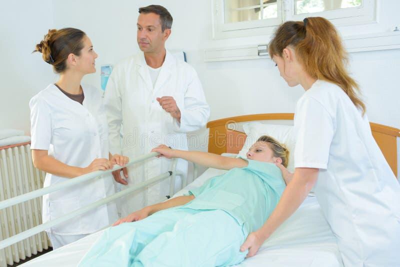 Пациент завальцовки медсестры сверх в больничной койке стоковые фото