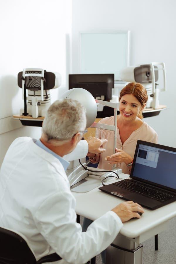 Пациент клиники частного сыщика усмехаясь пока говорящ для того чтобы врачевать стоковая фотография rf
