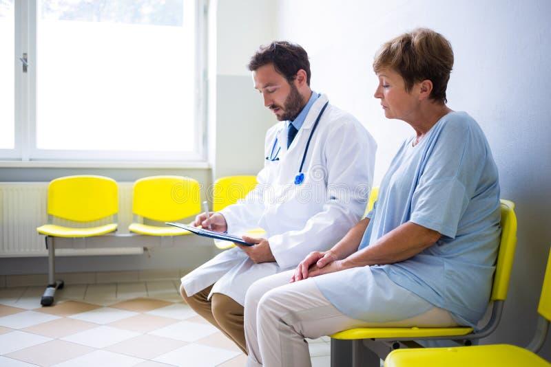 Пациент доктора советуя с в зале ожидания стоковые фото