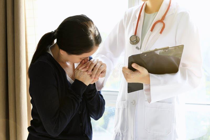 Пациент получая плохую новость, она отчаянна и плакать, поддержки доктора и утешать ее пациента стоковая фотография