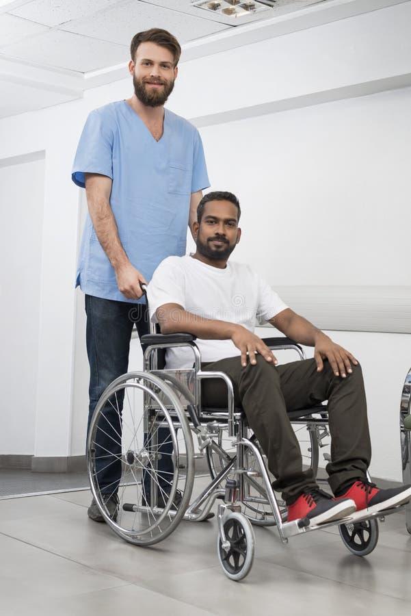 Пациент сидя в кресло-коляске пока медсестра стоя на больнице стоковое изображение