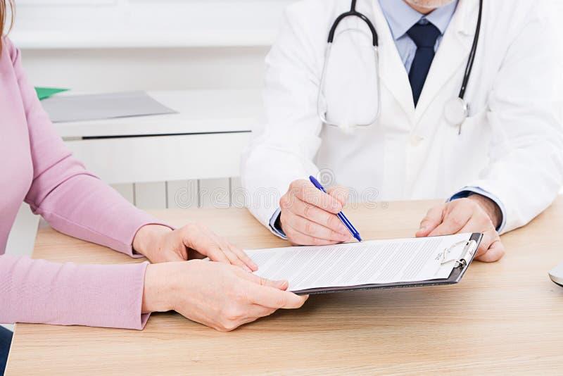 Пациент слушая умышленно к мужскому доктору объясняя терпеливые симптомы или спрашивая вопрос по мере того как они обсуждают обра стоковые изображения rf