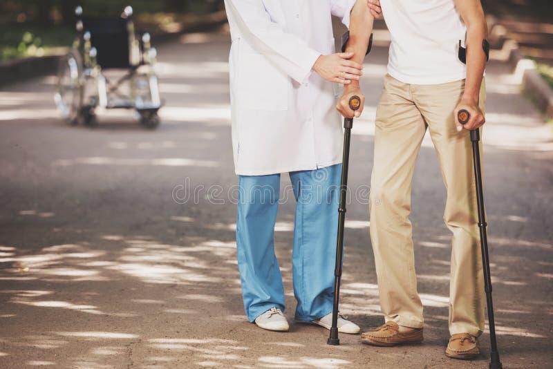 Пациент старика доктора Порции с костылями стоковое изображение