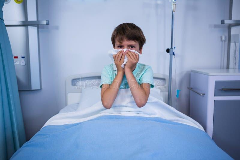 Пациент чихая его нос в палате стоковые изображения rf
