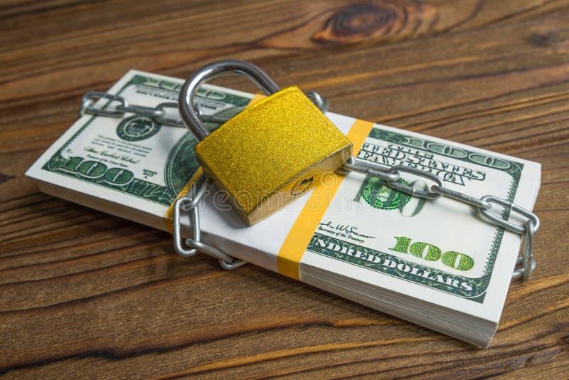 Пачка долларов денег банкнот, запертый замок с цепью стоковое изображение rf