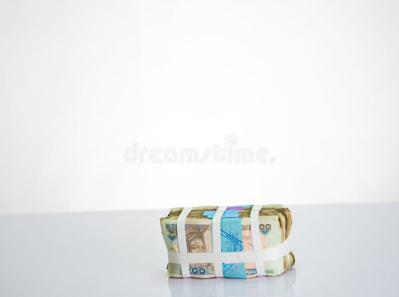 Пачки найры получают местные валюты наличными в белом ремне против белой предпосылки стоковые фото