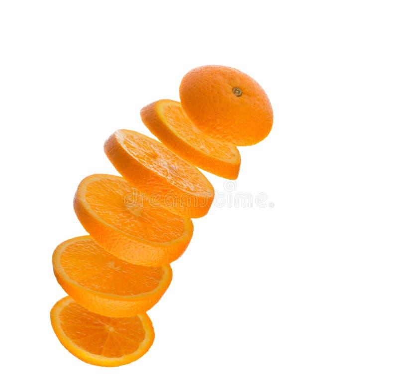 Падая куски апельсина в воздухе изолированном на белизне стоковые изображения