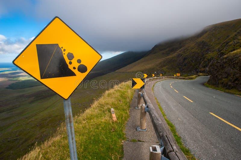 Падая предупредительный знак утесов на curvy дороге стоковые изображения