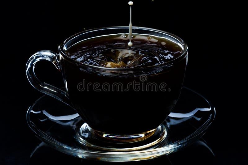 Падения молока понижаются в стеклянную чашку с черным кофе, черной предпосылкой стоковое фото rf