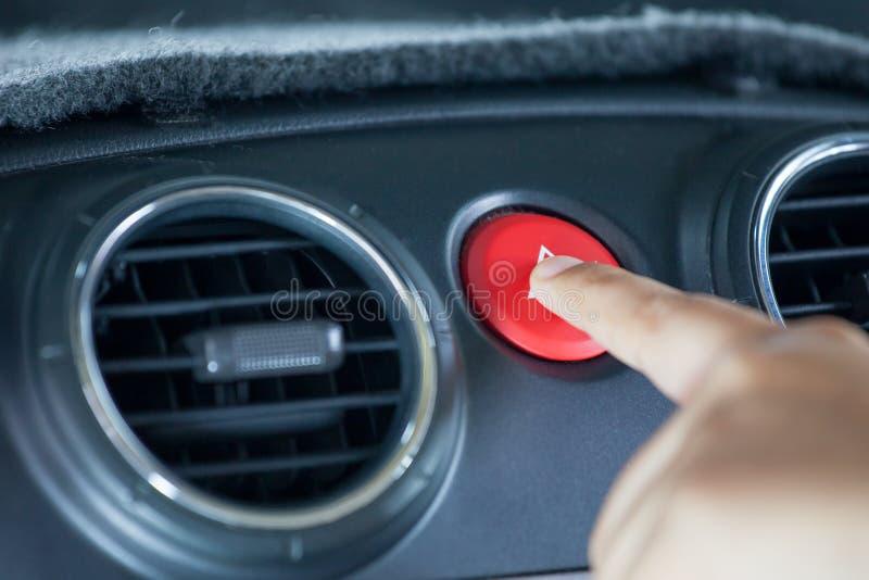 Палец женщины отжимая непредвиденную кнопку на приборной панели автомобиля стоковое фото