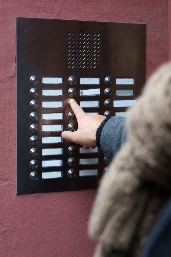 Палец отжимая дверной звонок на жилом доме стоковое изображение rf
