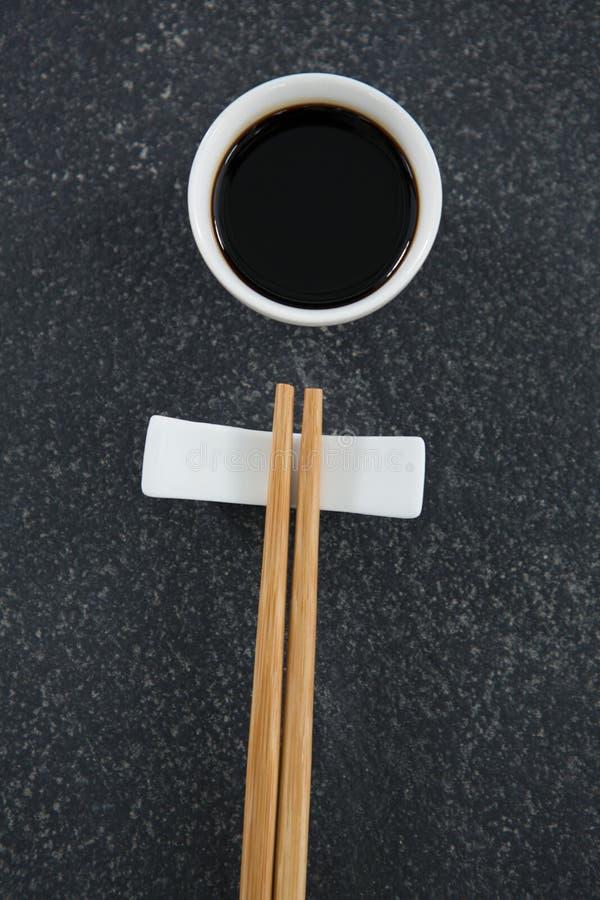 Палочки и соевый соус на каменной таблице стоковая фотография rf