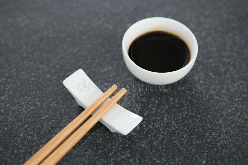 Палочки и соевый соус на каменной таблице стоковое фото rf