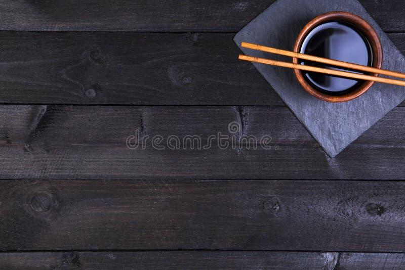 Палочки суш и соевый соус на черной предпосылке Взгляд сверху с космосом экземпляра стоковая фотография rf