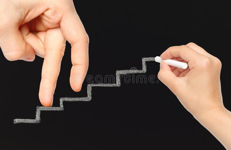 Пальцы на лестницах мела идут вверх пока рука с мелом стоковое фото rf