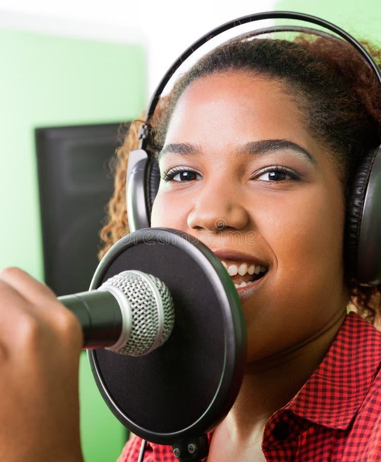 Певица выполняя в студии звукозаписи стоковая фотография rf