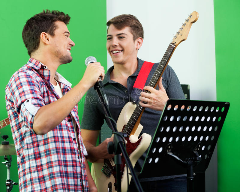 Певица выполняя пока смотрящ гитариста внутри стоковое фото rf