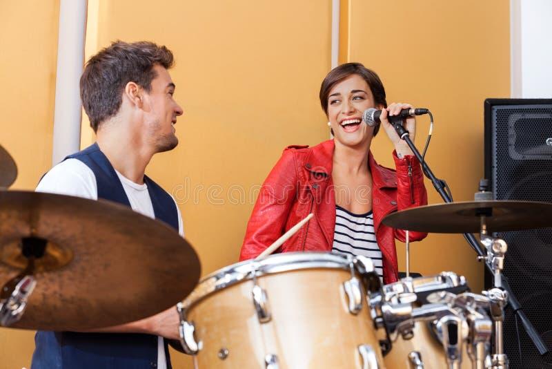 Певица выполняя пока смотрящ мужского барабанщика стоковая фотография rf