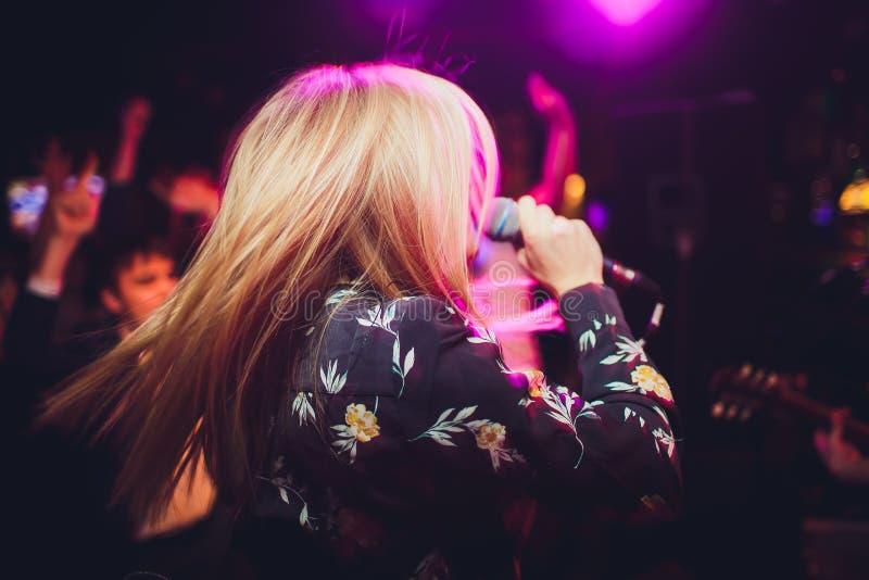 Певица девушки модели красоты с микрофоном поя и танцуя над предпосылкой праздника накаляя Певица партии караоке стоковые изображения rf