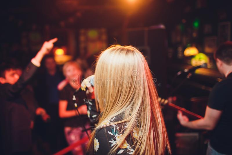 Певица девушки модели красоты с микрофоном поя и танцуя над предпосылкой праздника накаляя Певица партии караоке стоковое фото
