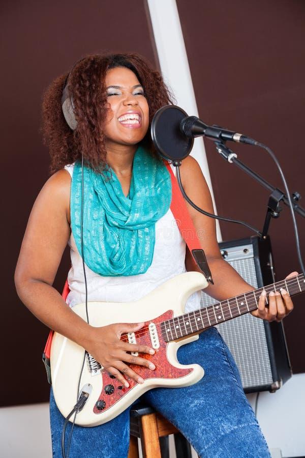 Певица играя гитару в студии звукозаписи стоковые изображения rf