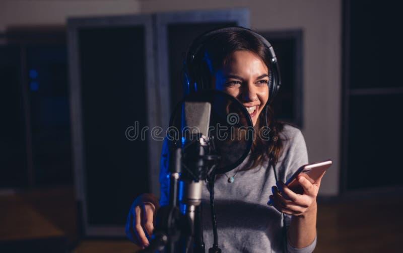 Певица поя в студии звукозаписи стоковое изображение rf