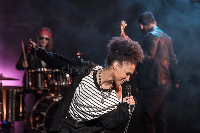 Певица при микрофон и диапазон рок-н-ролл выполняя музыку тяжелого рока стоковые фотографии rf