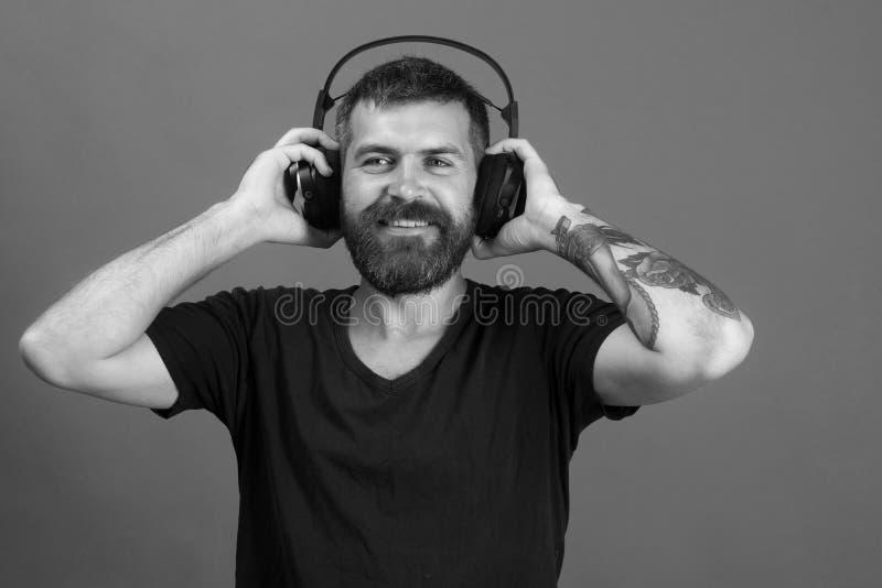 Певица с бородой и счастливой стороной слушает к музыке Человек держит наушники на голубой предпосылке Dj с бородой стоковое изображение