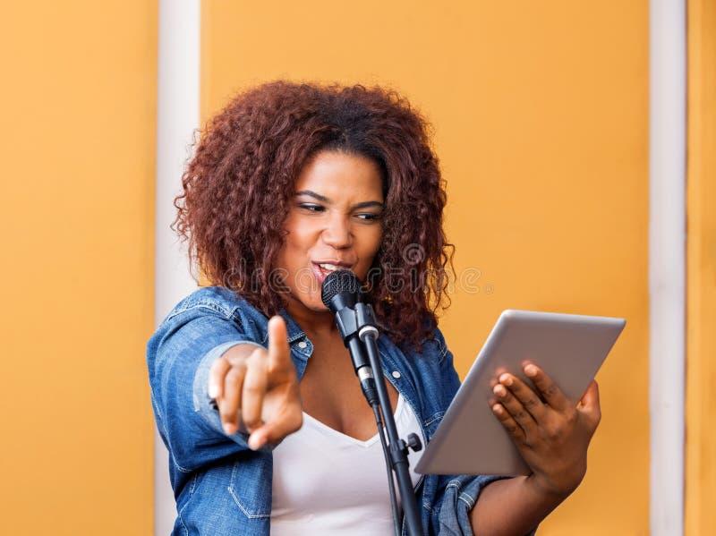 Певица указывая пока держащ таблетку цифров стоковое изображение
