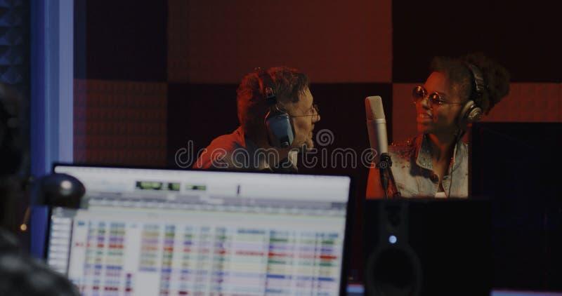 Певицы и звукооператор работая в студии стоковое изображение rf