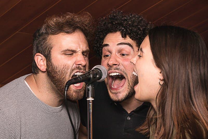 3 певицы поя с микрофоном с эйфоричным выражением стоковая фотография