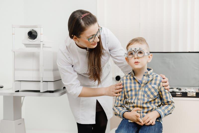 Педиатрический офтальмолог доктора проверяет зрение мальчика ребенка Выбор концепции объективов стекел стоковое изображение rf