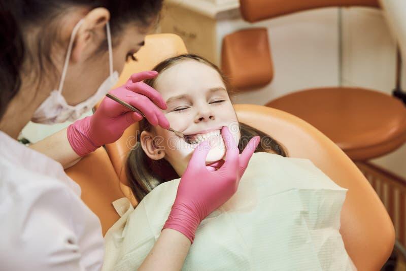 Педиатрическое зубоврачевание Дантист обрабатывает зубы маленькой девочки стоковые изображения rf