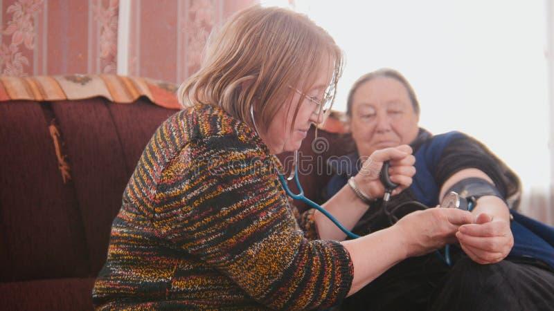 2 пенсионера - старшие дамы проверяя положение здравоохранения с манометром - давление измерений, пожилой образ жизни стоковые изображения rf